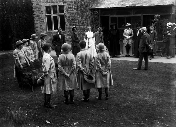 Nine members of the Women's Land Army standing on the lawn listening to Viscountess Falmouth during an official visit at Tregavethan Farm, a Women's Land Army training centre. Also included are Lady Ingeborg Molesworth-St Aubyn, Miss Henderson, Mr W