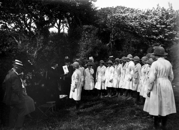 Members of the Women's Land Army being presented with their passing out certificates in front of a group of onlookers at Tregavethan Farm, a Women's Land Army training centre. The women's uniform consists of boots, gaiters, felt hats and pale fabric overalls