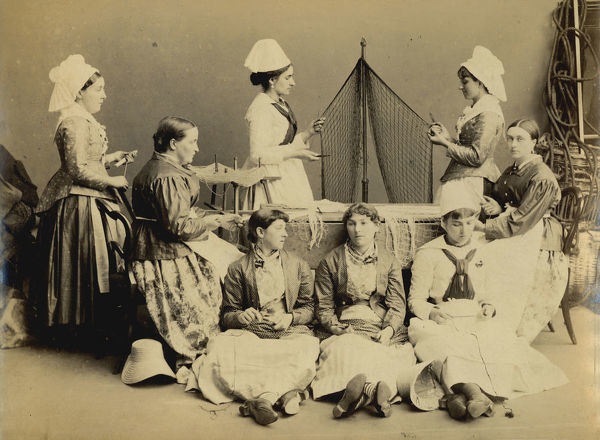 A posed group of eight women wearing traditional costumes and carrying out tasks associated with the fishing industry