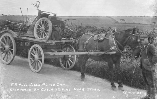 Mr A.W. Gill's motor vehicle on a cart after being destroyed by fire. Liskey Hill, Perranporth, Cornwall. June 1906