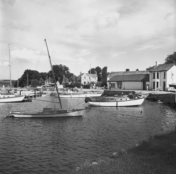 Various boats alongside the harbour wall, breakwater and pontoon with the yacht Sylvia in the foreground. Buildings and businesses on shore including Mylor Yacht Harbour Ltd. Photographer: Charles Woolf