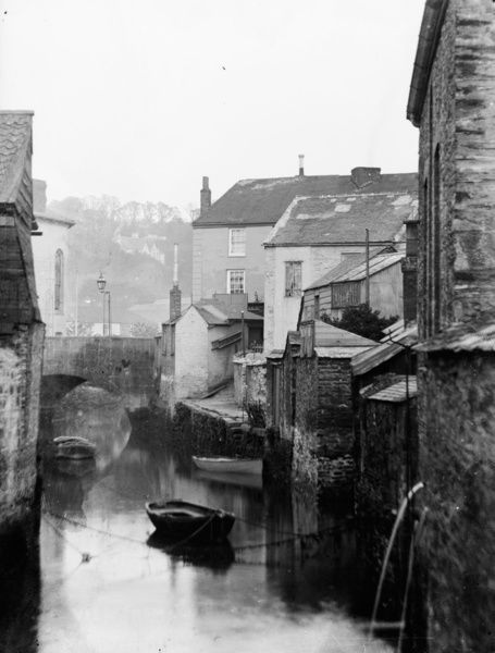 View of the New Bridge Street bridge from the Old Bridge Street bridge, showing small boats in the River Allen at high tide. L.R. Penhaligon, furniture dealer, of 19 New Bridge Street is partly visible. Photographer: Arthur Philp