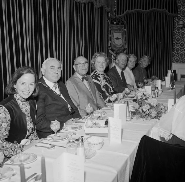 Seated for dinner, from left to right: Jessica Mann (1937-2018), novelist and broadcaster, also known by her married name Jessica Thomas; possibly Stuart Beard, Chairman of Newquay Old Cornwall Society; Charles Woolf (1907-1984)