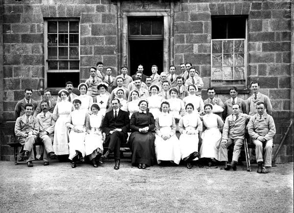 A large group of nurses and patients at the entrance to the hospital. Matron seated centre front, next to a man in a civilian suit. Photographer: Arthur William Jordan
