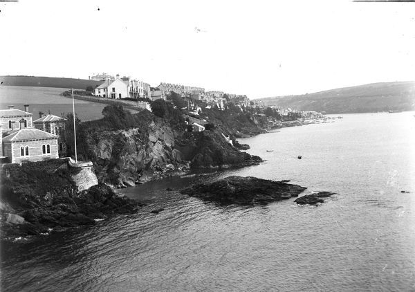 Rows of houses can be seen along the coast, along with boats in the harbour. Photographer: Unknown