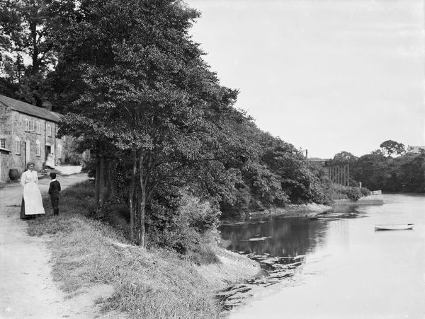 A view of Porth Navas showing some cottages with a lady and boy on the left, and the river down to the old jetty on the right. Photographer: Herbert Hughes