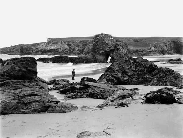 A view of the beach with a man, probably a member of the photographic party, standing among the rocks by the tideline. The rock arch was destroyed by storms in 2014. Photographer: John Charles Burrow