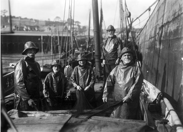 Porthleven fishermen in their boat by Newlyn Harbour wall. All aged over 70, they returned to fishing during the manpower shortage in the First World War. Photographer: Arthur William Jordan