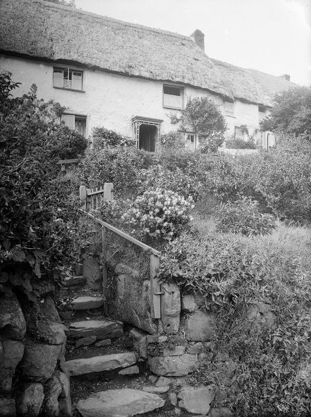 A view of stone steps leading up to a row of thatched cottages. Photographer: Herbert Hughes