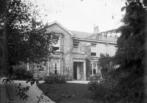 "A view of the rear of Goonvrea House through the trees. In 1980, Rex Barratt writes in his book, Stately Homes in and Around Truro, ""Goonvrea, probably built by the Fox family of Falmouth and later owned and occupied by Sir Frederick Martin Williams, M"