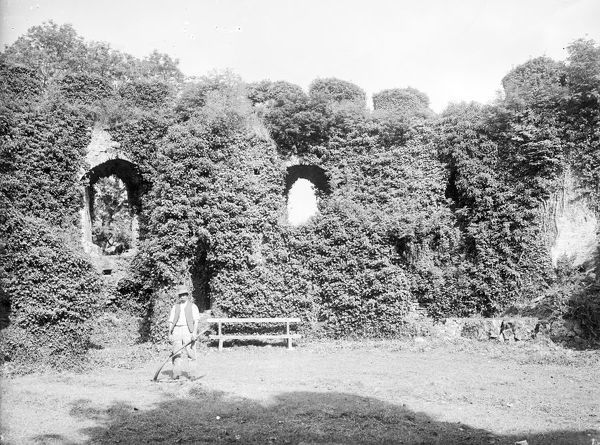 A man stands in front of the ivy clad ruins of Restormel Castle while holding a scythe. Photographer: unknown