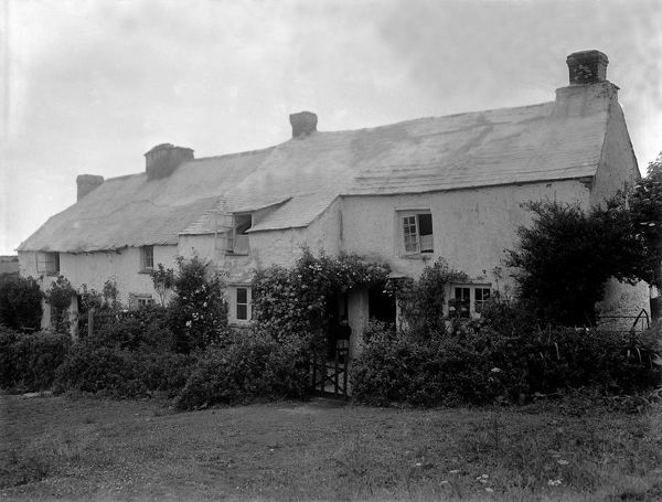 A general view of Rose Cottage at Tregurrian. A young boy is standing in the doorway. Photographer: Herbert Hughes