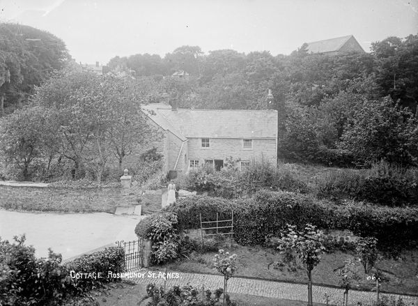 Showing the garden of another property in the foreground and a lady standing at the gateway of the cottage garden behind. Photographer: Unknown