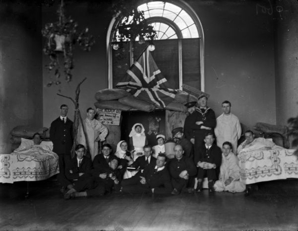 Sailors and nurses in Chellew Ward with a scene set up. The notice reads The better 'ole if you know of a better ward go to it. Photographer: Arthur William Jordan