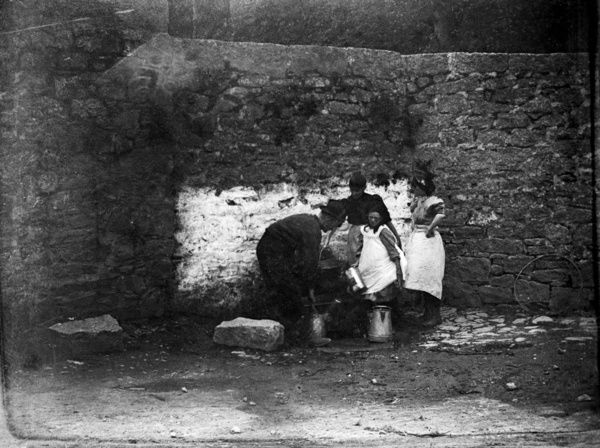 A group of four people filling buckets by a well. Probably St Ia's Well at the foot of Porthmeor Hill. St Ia was supposedly an Irish Princess who brought Christianity to the area in about AD 500. St Ives is a derivative of her name. Photographer: S