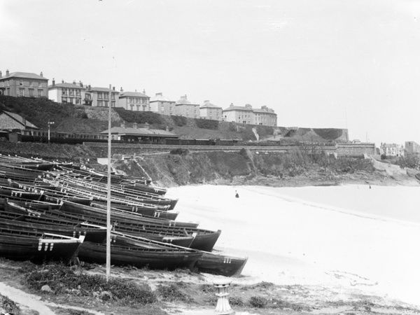 St Ives Railway Station from Porthminster beach. A fleet of seine boats are drawn up on the beach below. Photographer: Unknown