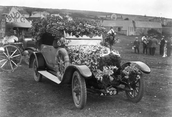 A Standard car that won the first prize for a decorated motor. The car was decorated with sweet peas and rambler roses. Possibly by W. Robinson? The licence plate number was AF69. Unknown location. Photographer: Arthur William Jordan