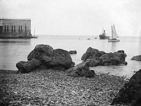 View, on the left, of stone barges at the quarry jetty, taken from the beach. A tug and yacht with some rowing boats can be seen further out. Photographer: Arthur William Jordan