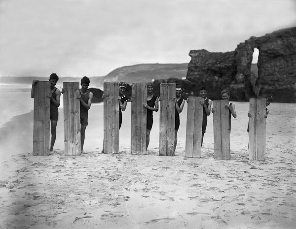 Eight surfers posing with boards on the beach. Retreat Rocks are in the background. Photographer: Arthur William Jordan