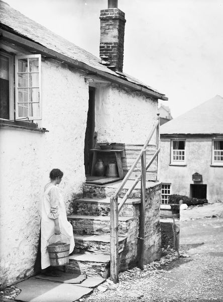 Teresa Mallett is standing at the foot of the steps of a cottage, carrying a wooden barrel pail