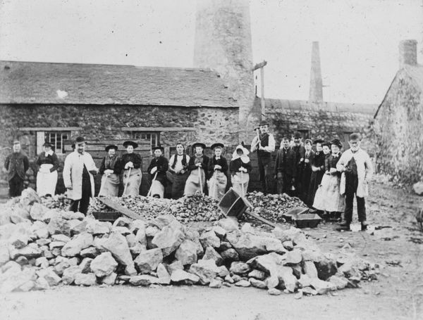 Miners and bal maidens posed in front of surface buildings. Part of the A.K. Hamilton Jenkin collection. Photographer: Unknown