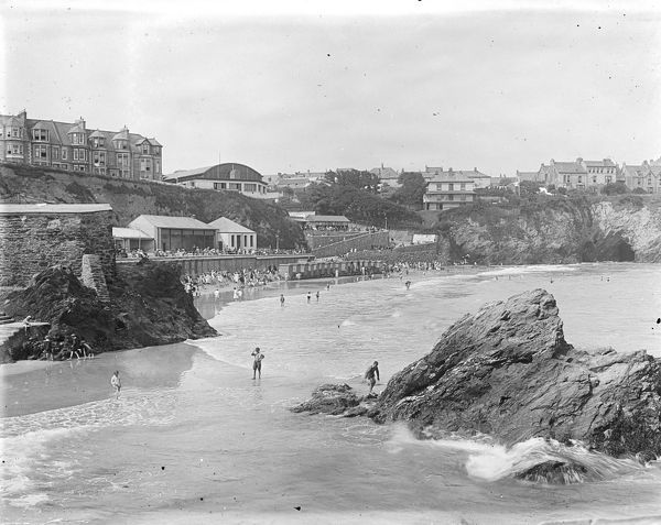View of Towan Beach and the promenade with bathers and a line of wheeled bathing machines. Photographer: Unknown