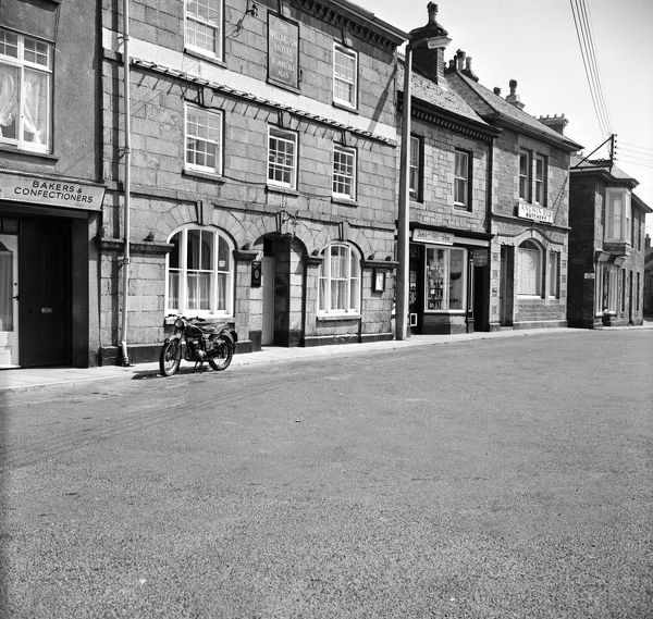 A view of the Wellington Hotel in Market Square (or Commercial Square) looking along to Andy's Gift Shop and Angwin Brothers the butchers on the right. Part of Warren and Son bakers and confectioners can be seen on the left. Photographer