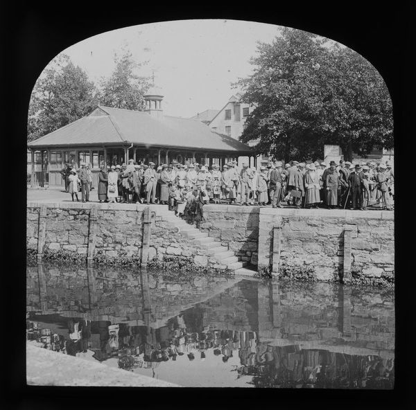 A glass lantern slide picturing a large group of excursionists waiting for an excursion steamer on the Truro River at Worth's Quay. The refreshment pavilion, seen on the left with a datestone of 1911, was later demolished to allow for widening of the road