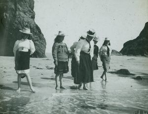Perranporth Arch Rock, six ladies paddling on the beach. Cornwall