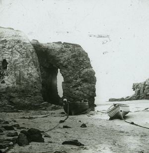 Perranporth Arch Rock, with boats on the beach, Cornwall. Around 1925