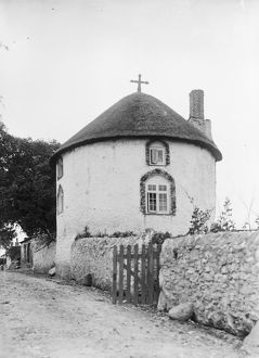 A white painted thatched round house with a cross, Veryan, Cornwall. 1911